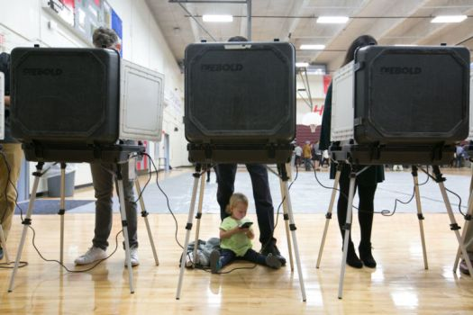 ATLANTA, GA - NOVEMBER 06: Sloane (no last name given), 2, waits between her father's legs as he and other voters cast their ballots at a polling station set up at Grady High School for the mid-term elections on November 6, 2018 in Atlanta, Georgia. Georgia has a tight race to elect the state's next governor and a lot of worries over voting security. (Photo by Jessica McGowan/Getty Images)