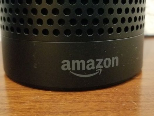 Close-up of the base of an Amazon Echo smart speaker using the Alexa service, with Amazon logo visible, on a light wooden surface, San Ramon, California, May 31, 2018.