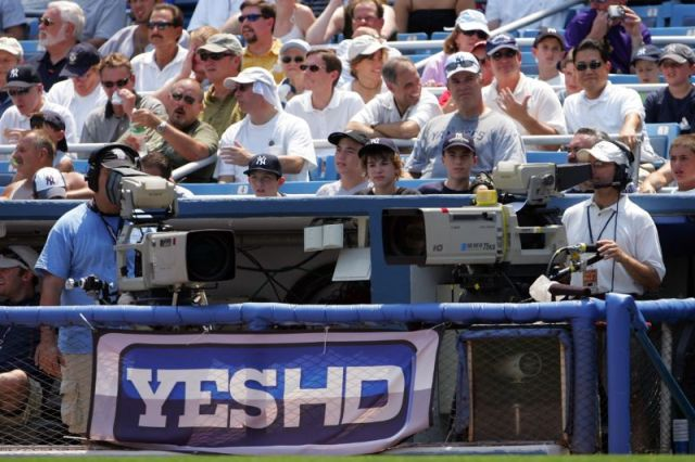 TV cameramen and a YES network logo banner at Yankee Stadium.