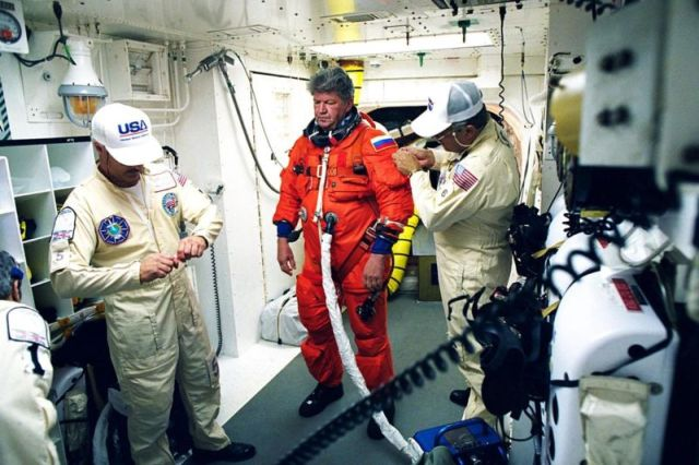 In 1998, STS-91 Mission Specialist and Russian cosmonaut Valery Victorovitch Ryumin is assisted with his flight suit prior to his entry into the space shuttle <em>Discovery</em>.