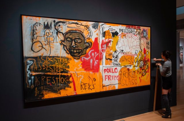 A Sotheby's employee hangs a name plate near Jean-Michel Basquiat's<em>Untitled (Pollo Frito)</em>on November 2, 2018, at Sotheby's Auction house in New York