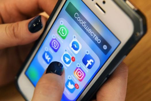 A woman holds a smartphone with icons for social networking apps Facebook, Instagram, Twitter and others. The app icons are in a folder whose title is the Russian word for