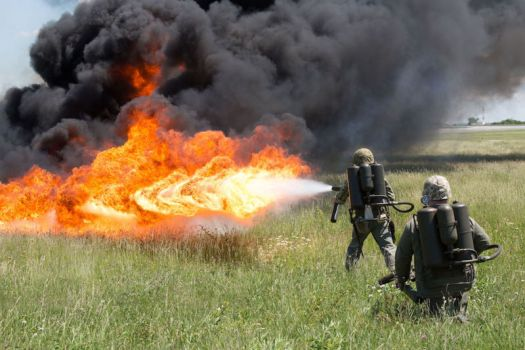 Marines use flamethrower to spectacular effect in field.