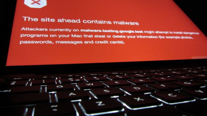 A laptop monitor warns of an impending encounter with malware.