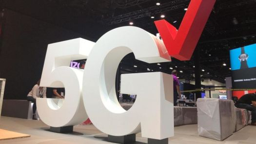 A giant Verizon 5G logo in an expo hall.