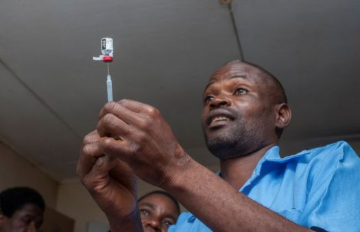 A man stabs a needle into a jar of liquid.