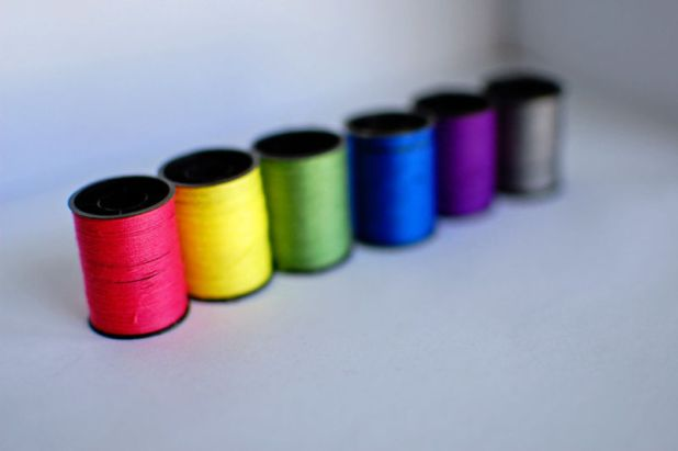 Different-colored rolls of thread are lined next to each other.