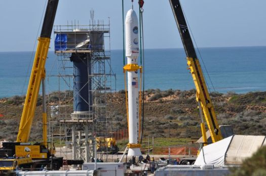 At Vandenberg Air Force Base in 2009, two cranes have raised NASA's Orbiting Carbon Observatory, or OCO, spacecraft to vertical. OCO would later be lifted and attached to the waiting Stage 0 motor of the Taurus XL launch vehicle in the tower.