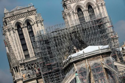 Protective tarps displayed on the roof of Notre-Dame de Paris cathedral, two weeks after a fire devastated it in Paris.