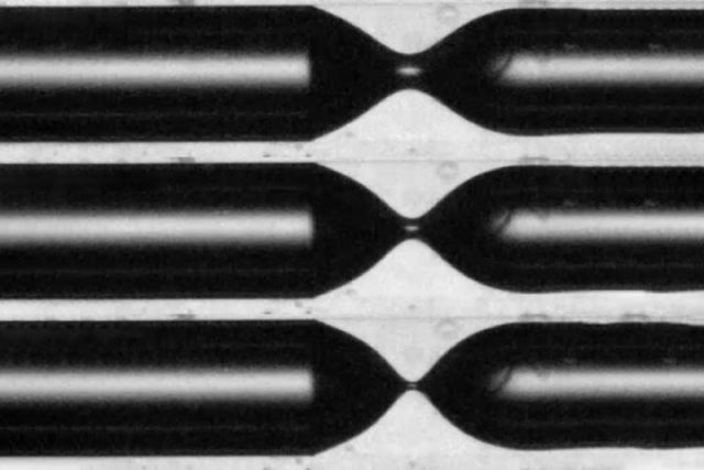 """This series of images shows the process of """"pinch-off"""" in which the air bubble (black) starts to separate off as it penetrates into a liquid environment (white) inside a narrow tube."""