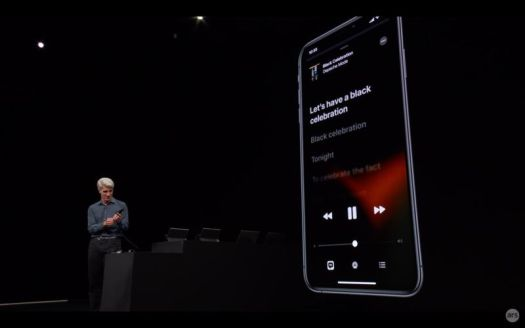 Apple Senior VP Craig Federighi on stage, showing an iPhone with iOS 13's dark mode.