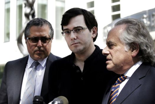 Three men stand behind microphones.