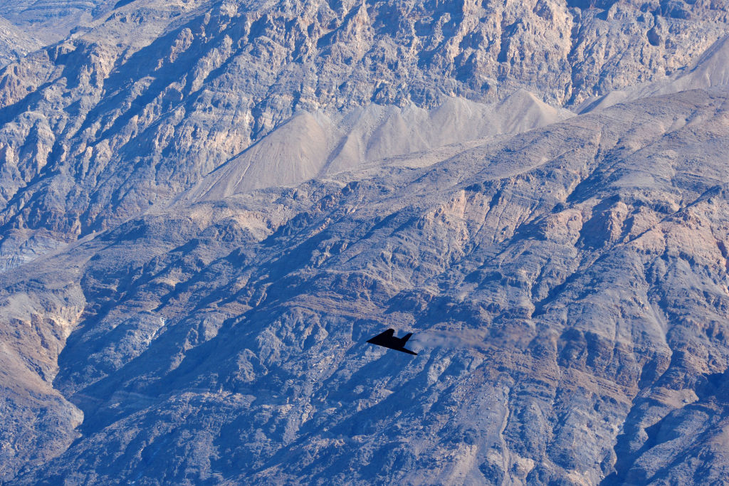 """An F-117 Nighthawk Stealth Fighter flies near the """"Jedi Transition"""" on February 27, 2019 in Death Valley, California."""
