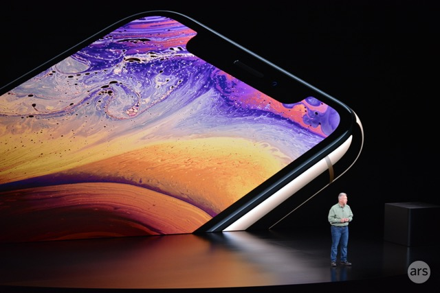 A man on a stage is dwarfed by a gigantic video display of a smartphone.