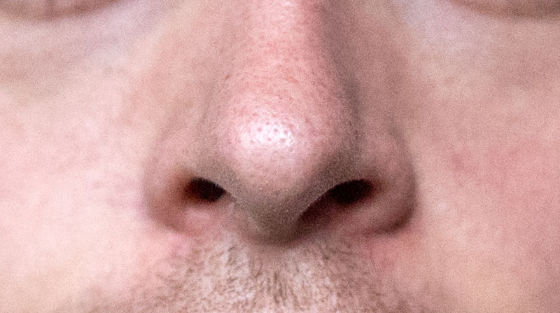 Extreme closeup photograph of a man's nose.