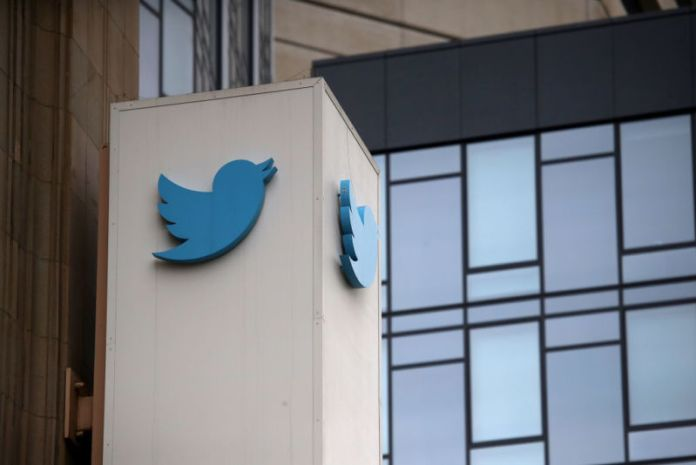 Exterior of glass-walled office building with Twitter logo on a column.