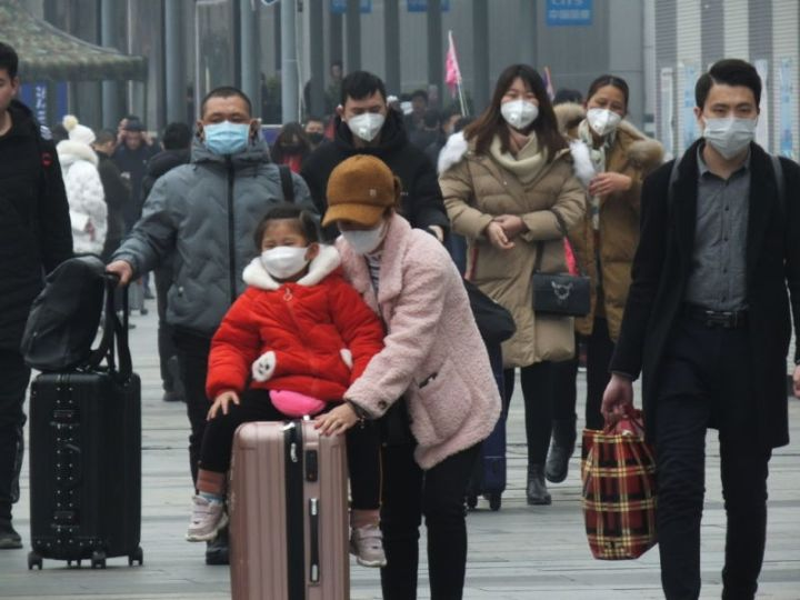 Images of people wearing respiratory masks in a Chinese railway station.