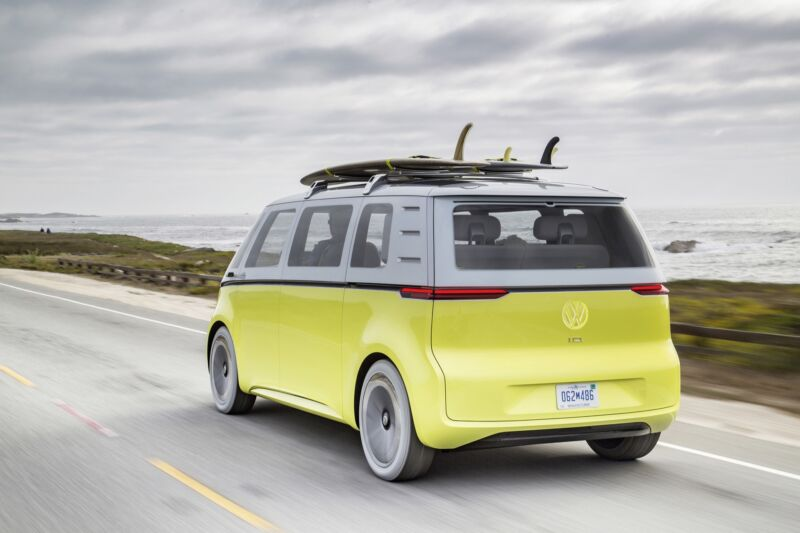 A yellow VW bus concept car drives past the beach, with surfboards on its roof