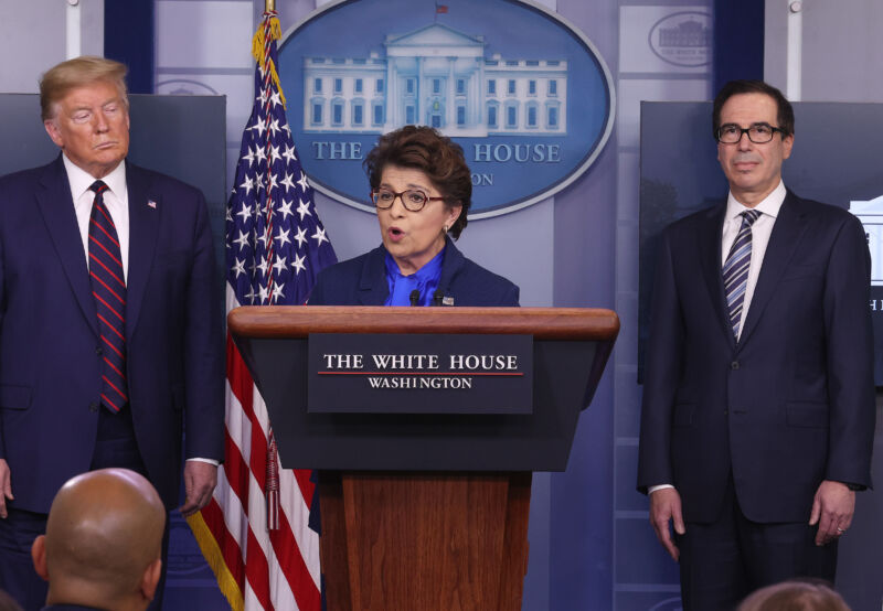 Three people stand by a podium in front of the White House logo.