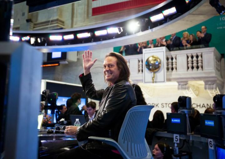 T-Mobile CEO John Legere sitting in a chair and waving at the camera.