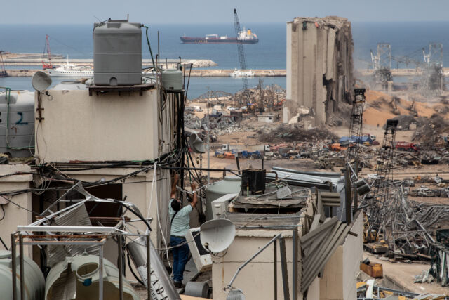 A man tries to fix an electricity cable on the damaged roof of an apartment block facing the Beirut port on August 13, 2020.