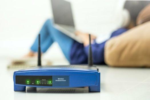 A wireless router seen near a woman using a laptop.