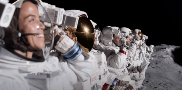 Astronauts stand in a row on the lunar surface.