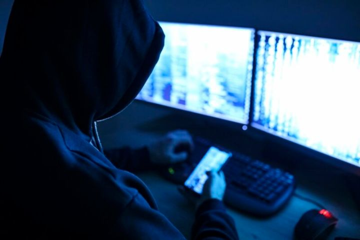A hacker sitting in front of two computer screens and holding a smartphone.