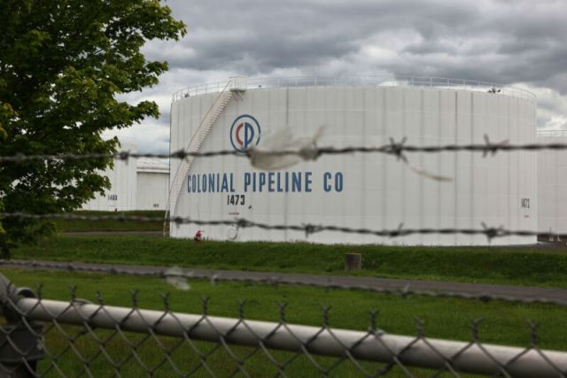 A chainlink fence separates us from fossil fuel tanks.