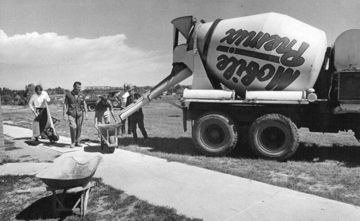 Black-and-white photograph of cement mixer at work.