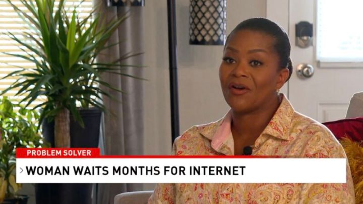 A woman sitting at home and talking to a news reporter. On screen, text says,