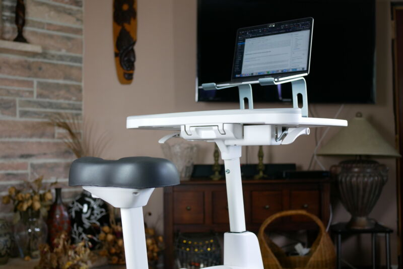 the bike seat and desktop of the desk bike with a laptop and wireless keyboard on top