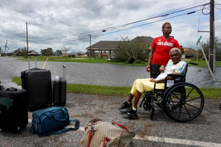 An elderly woman in a wheelchair and her daughter waiting for transportation in a flooded neighborhood.