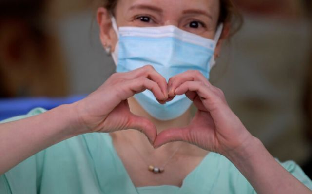 A masked woman makes a heart symbol with her hands.