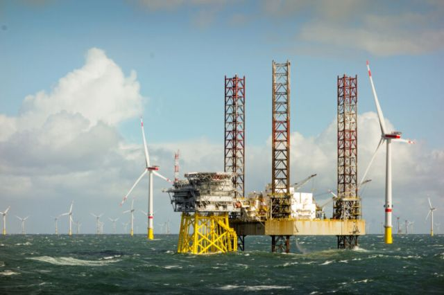 Image of a construction platform above the waves amidst wind turbines.