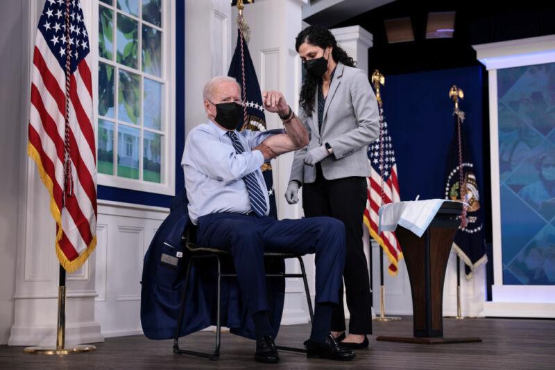 President Joe Biden rolls up his sleeve before receiving a third dose of the Pfizer/BioNTech COVID-19 vaccine