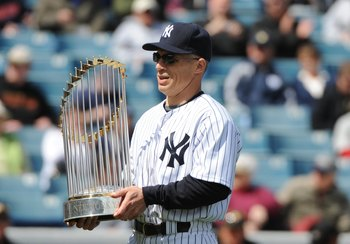 TAMPA, FL - MARCH 3: Manager Joe Girardi #28 of the New York Yankees carries the World Series trophy before play against the Pittsburgh Pirates on March 3, 2010 at the George M. Steinbrenner  Field in Tampa, Florida. (Photo by Al Messerschmidt/Getty Image