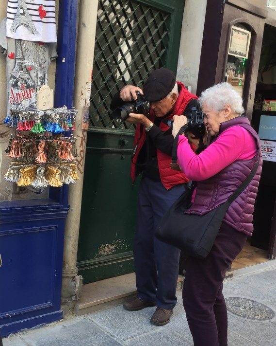 Photographers stop to photograph key rings for sales on the street in Paris, France.