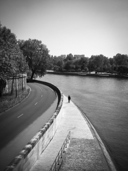 A man walks the banks of the Seine River in Paris, France.