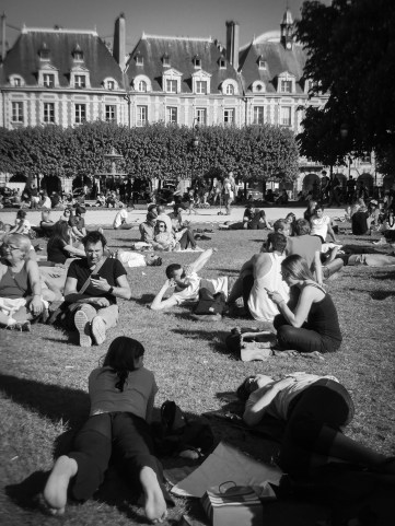 People fill the lawn of a park in Paris, France.