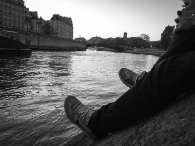 A man rests his feet on the side of the bank of the Seine River in Paris, France.