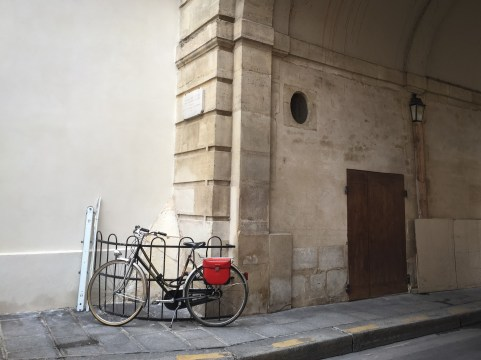 A bicycleswith red leather panniers on the street in Paris, France.