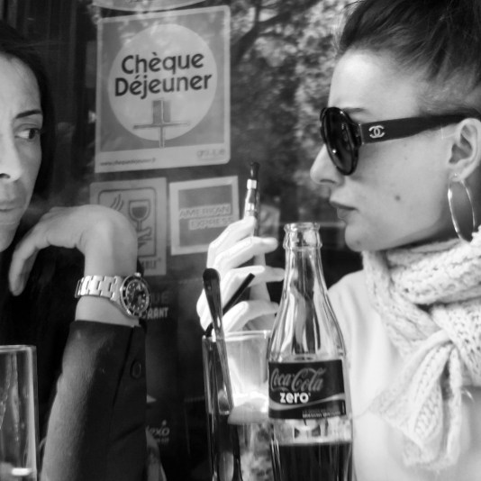 Two women enjoy a drink at a cafe in Paris, France.