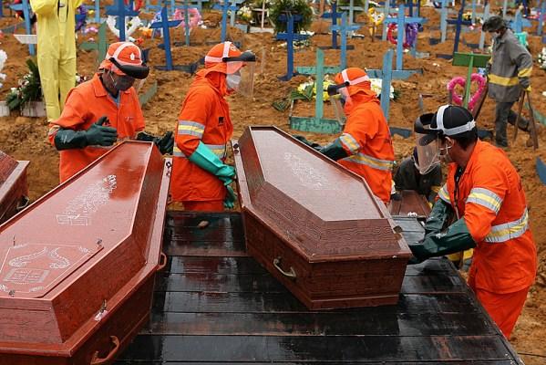 Caixões sendo descarregados para serem enterrados em uma vala comum no cemitério de Nossa Senhora em Manaus, estado da Amazônia