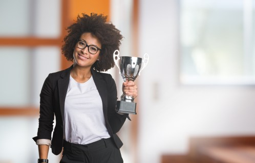 an employee holding a small trophy