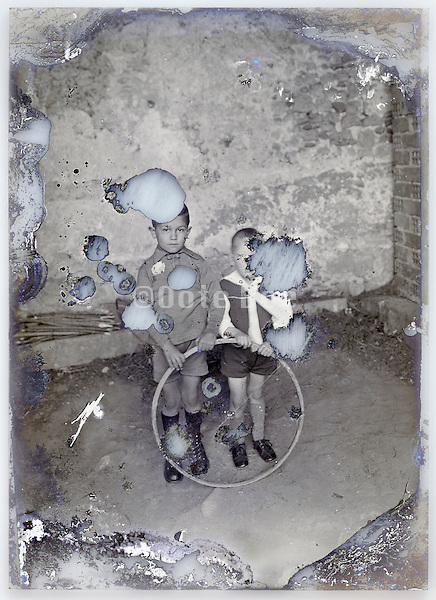 eroding glass plate with two little children holding a bicycle wheel