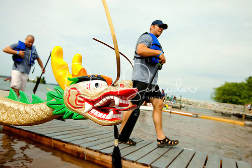 The head of a dragon boat with competitors walking along the dock behind.