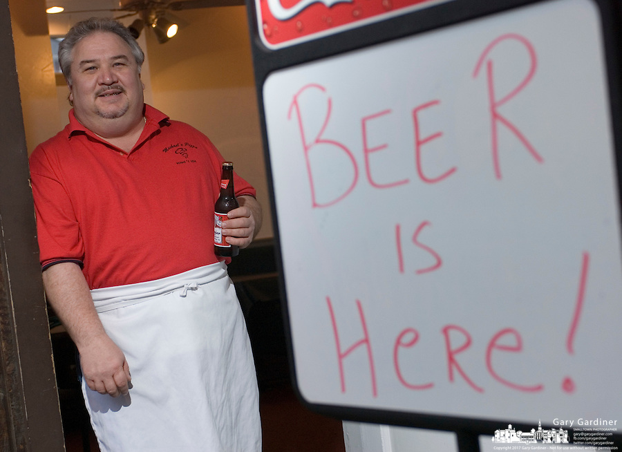 Michael Evans, owner of Michael's Pizza, holding a beer next to a sign that says