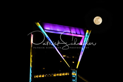 Full moon rising over Duke Energy Tower in Charlotte NC