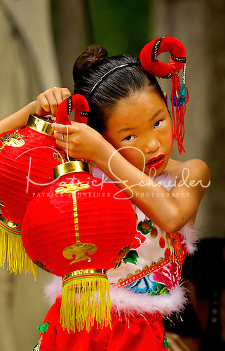 A young performer fiddles with her costume before going on stage at the Charlotte Asian Festival 2012 event.